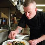 Grove's Chef de Cuisine, Chris North, prepares seed-crusted trout. Photo by Johnny Quirin