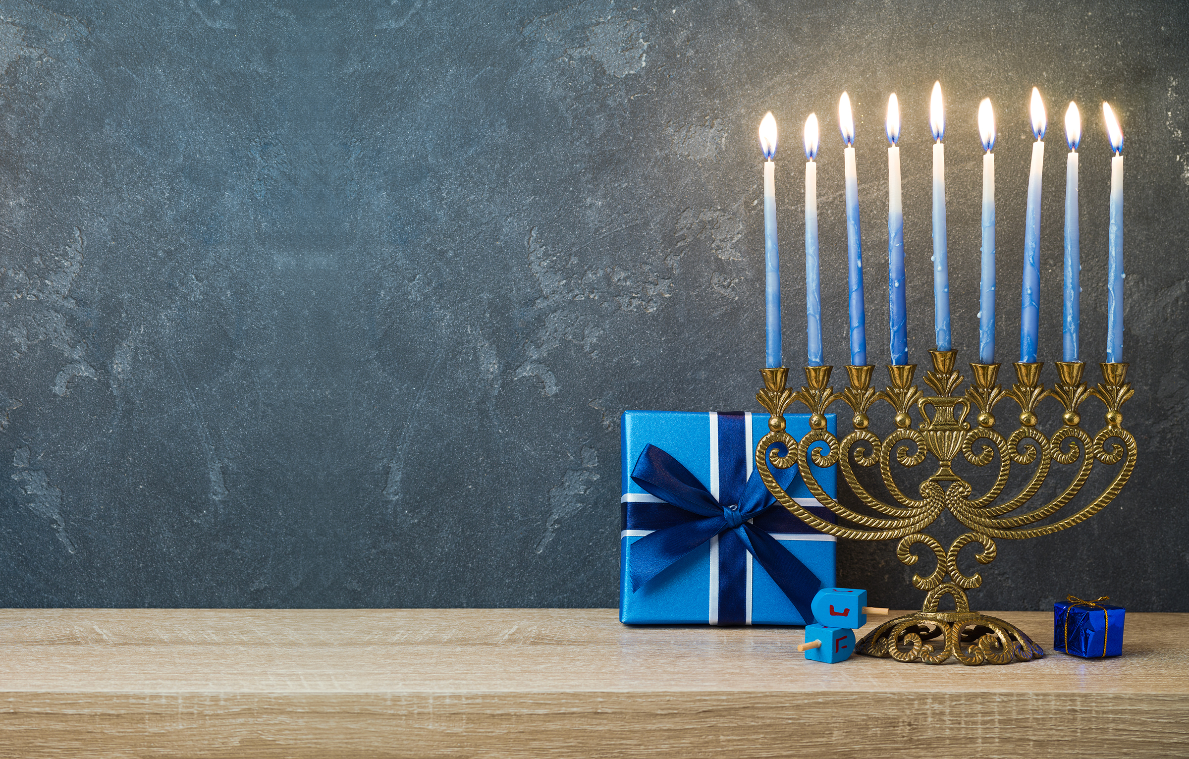Hanukkah celebration with menorah, gift box and dreidel on wooden table over blackboard background