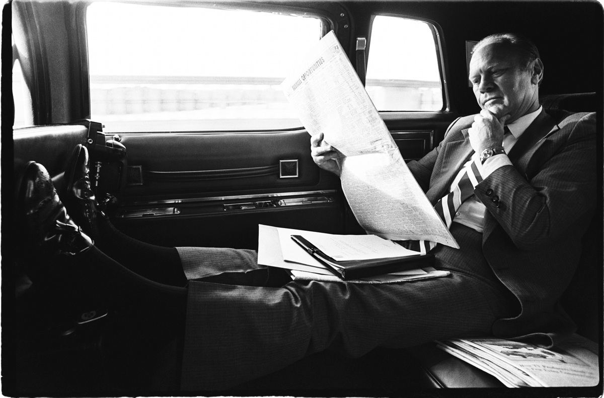 President Gerald R. Ford reading newspaper in car by David Hume Kennerly